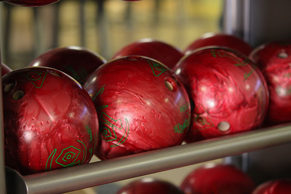 Red 10 pound bowling balls sitting on a bowling ball rack