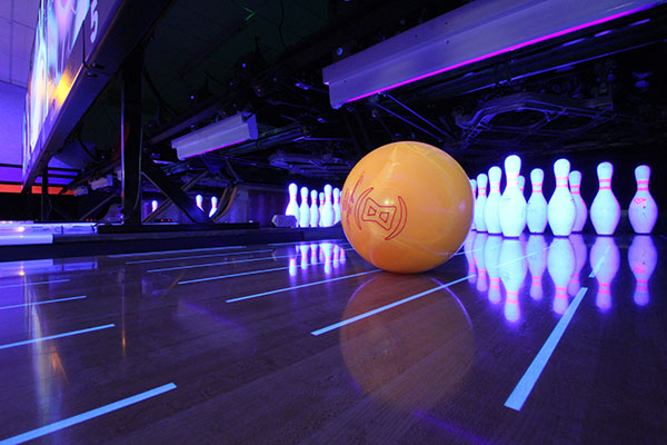 Orange 8 pound bowling ball on the lane, right before it hits the pins
