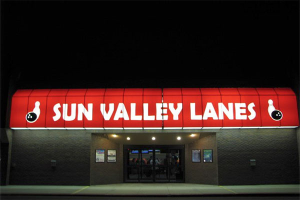 Sun Valley Lanes entrance at night with the Sun Valley Lanes awning lit up